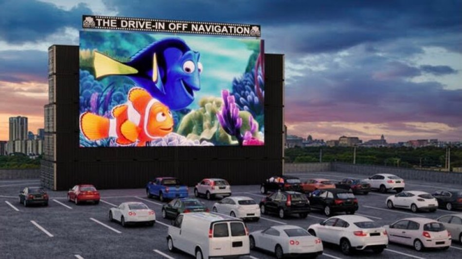 A photo of a drive in movie with cars facing a giant screen playing a cartoon movie.