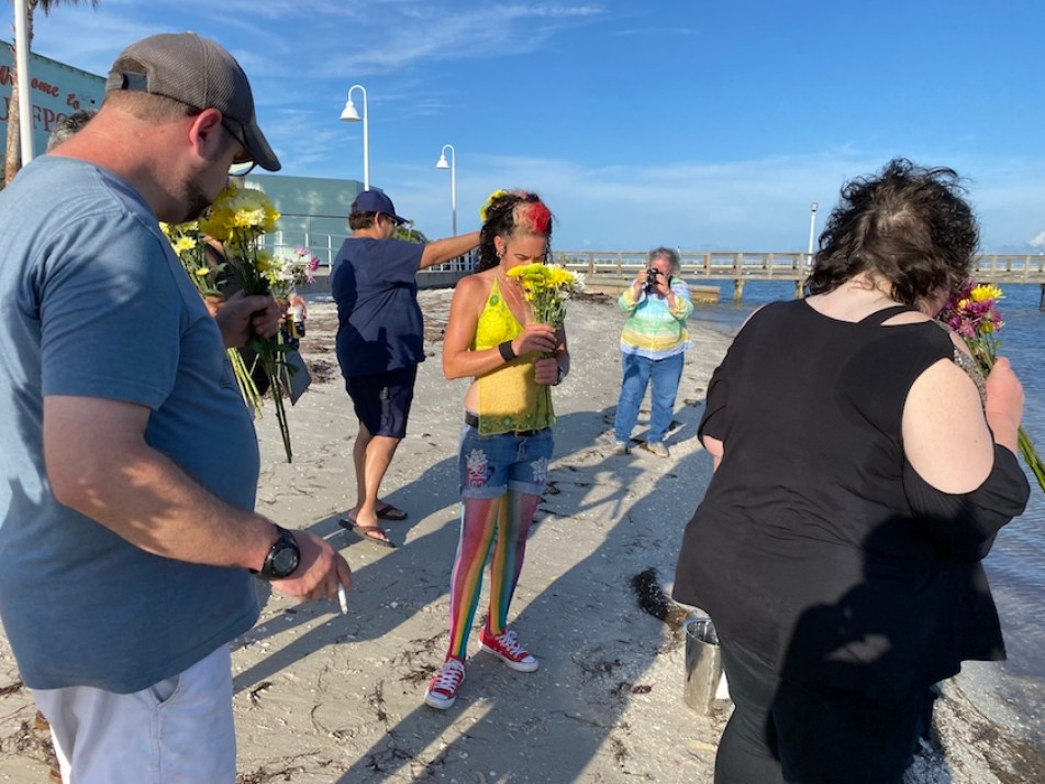 A woman in a small group of people on a beach holding a bouquet of flowers.