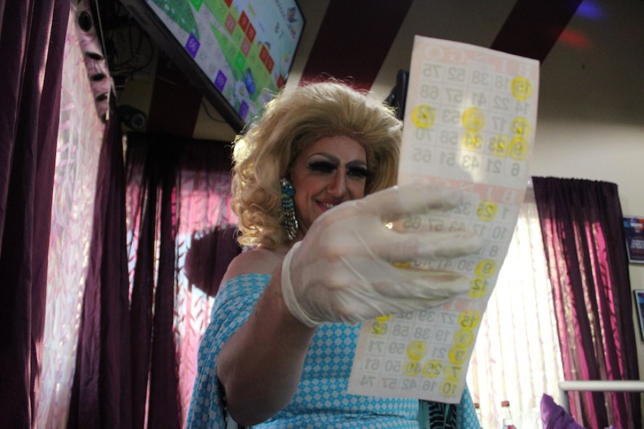A drag queen in a blue dress and blonde hair holds up a bingo sheet with a gloved hand.