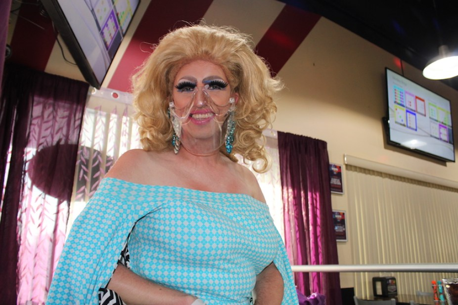 A drag queen in a blue dress and clear face mask.