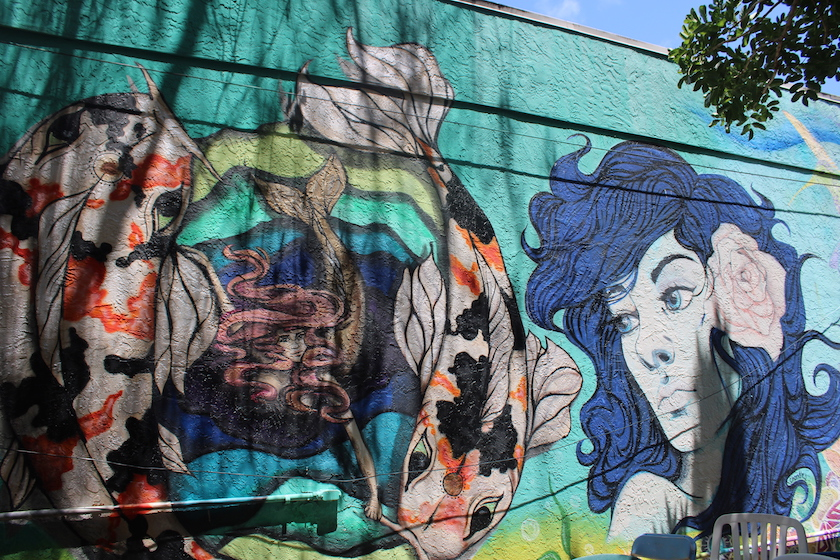A colorful mural featuring a woman with blue hair.