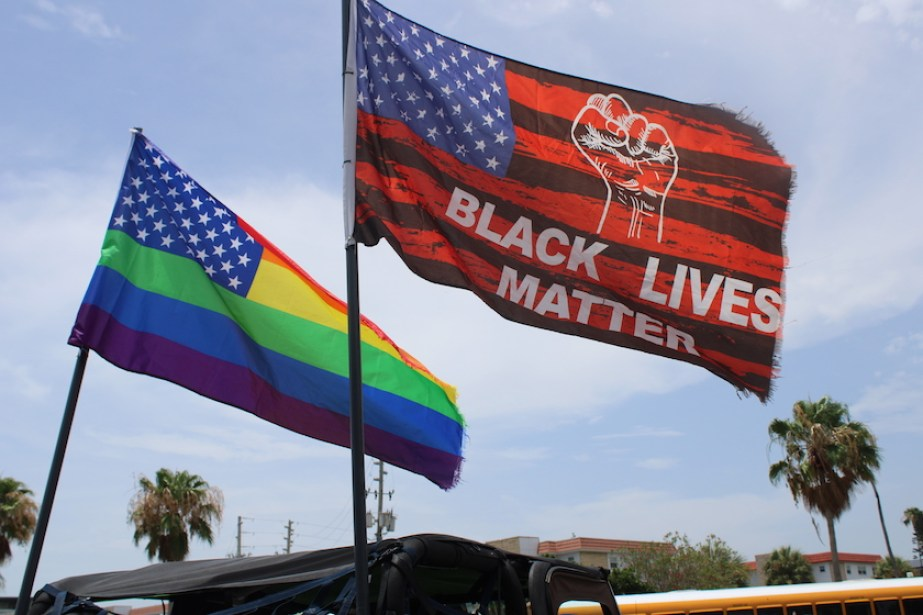 A photo of a rainbow US flag and a red Black Lives Matter US flag.