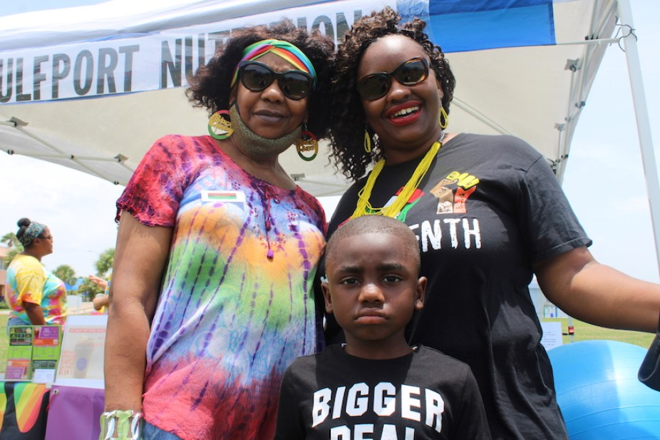 A photo of two women in t-shirts and sunglasses and a young boy smiling at the camera.