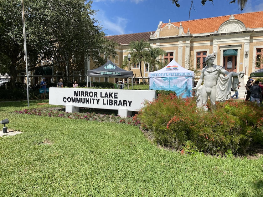 """A sign on a green lawn in front of an older building that reads """"Mirror Lake Community Library."""""""
