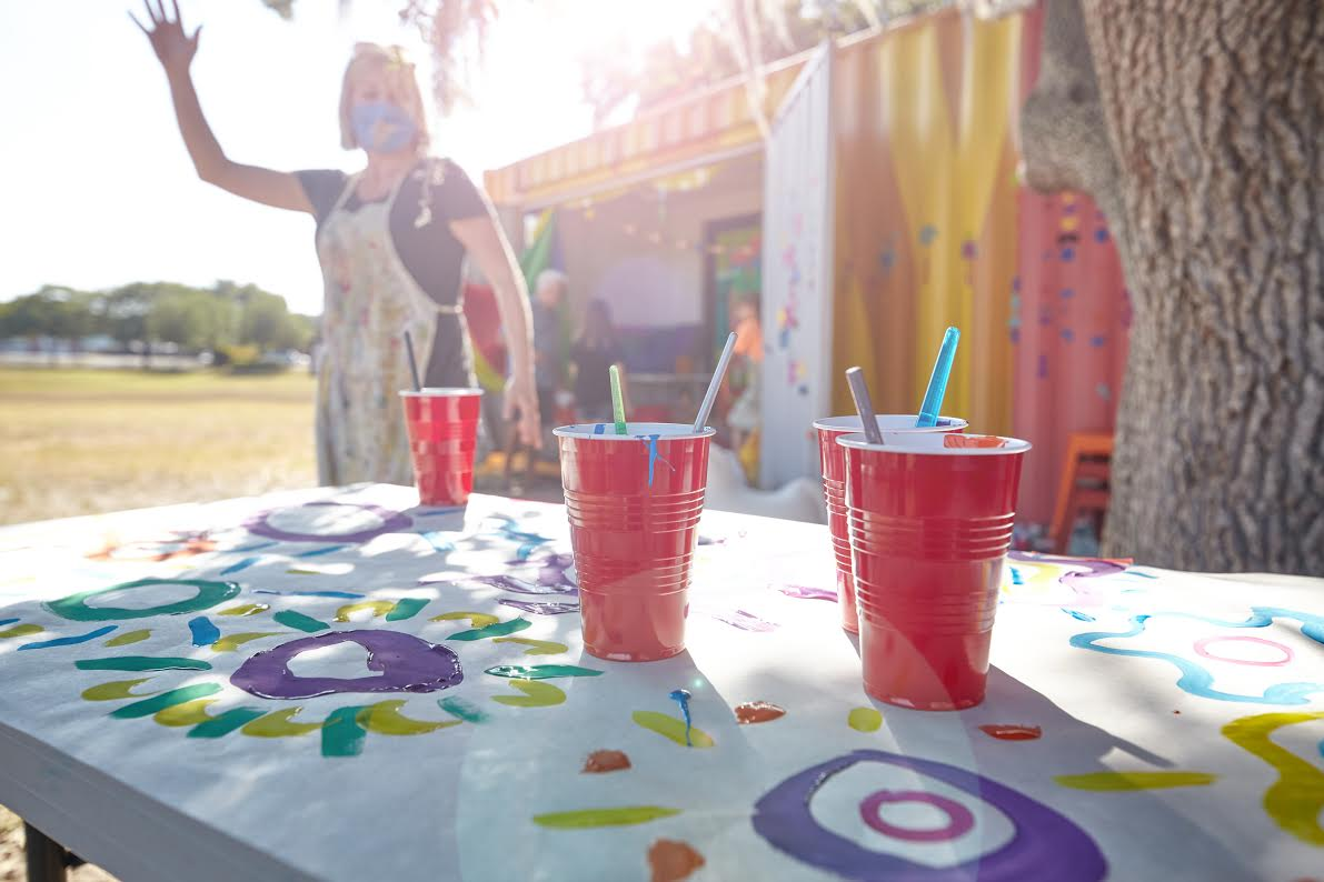 A photo of red cups on a table with paintbrushes in them and a woman in an apron painting in the background.