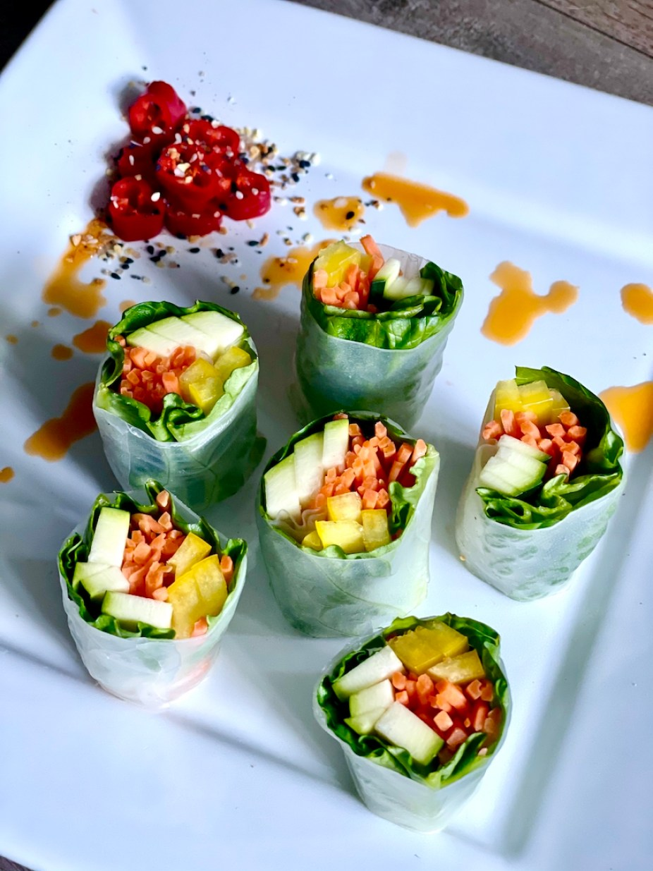 A photo of vegetable spring rolls on a white plate with red chillies and orang sauce.