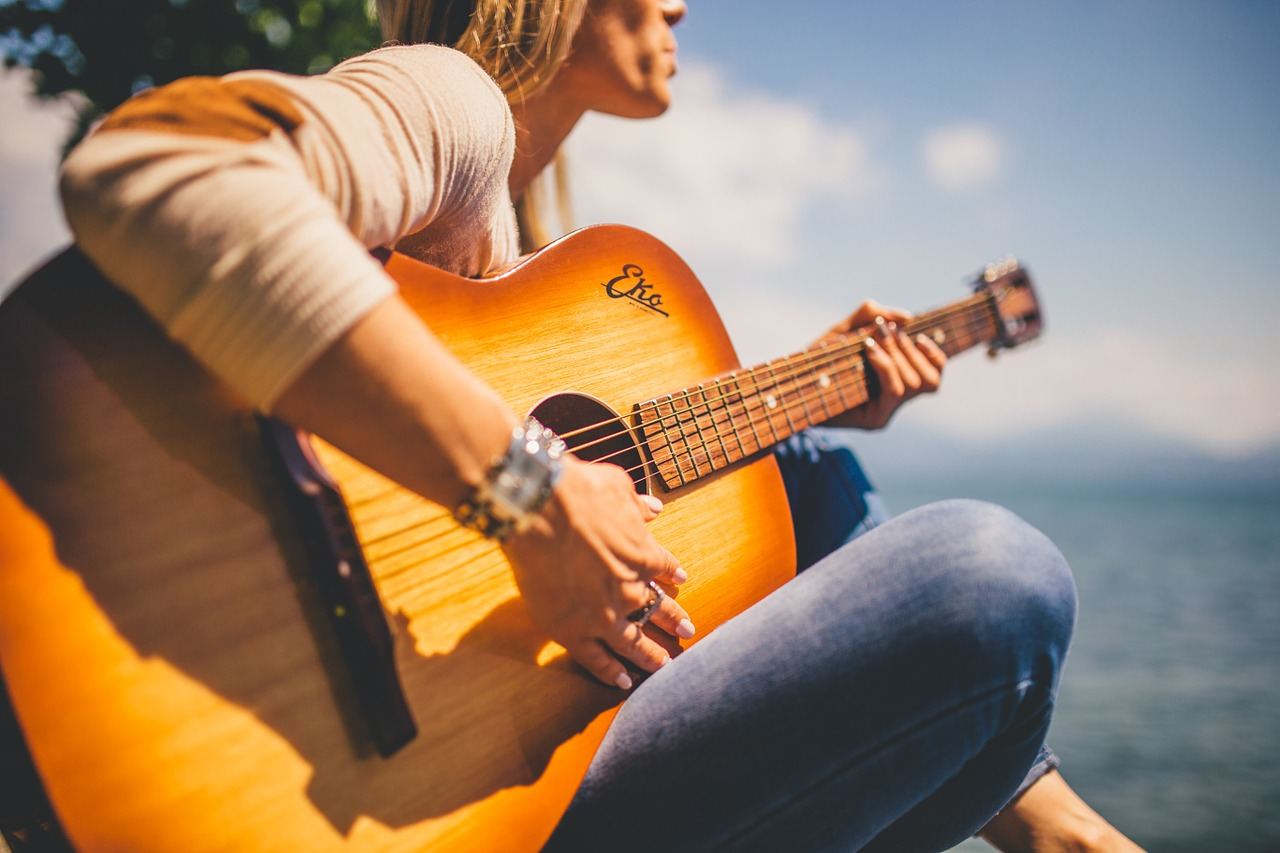 A close up photo of a woman playing a brown acoustic guitar outside.