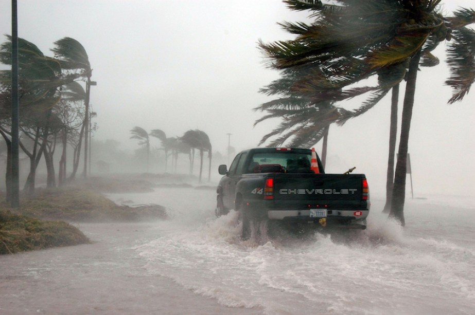 A photo of a truck driving though a severe, windy storm near a beach.