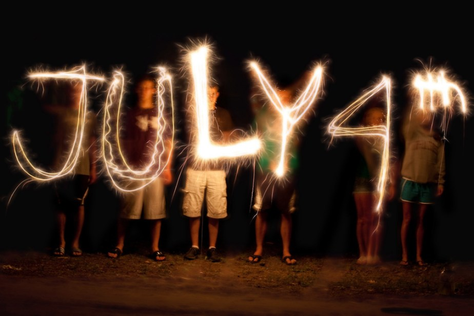 """A """"light drawing"""" with four people in the dark using sparklers to spell out """"July 4th"""""""