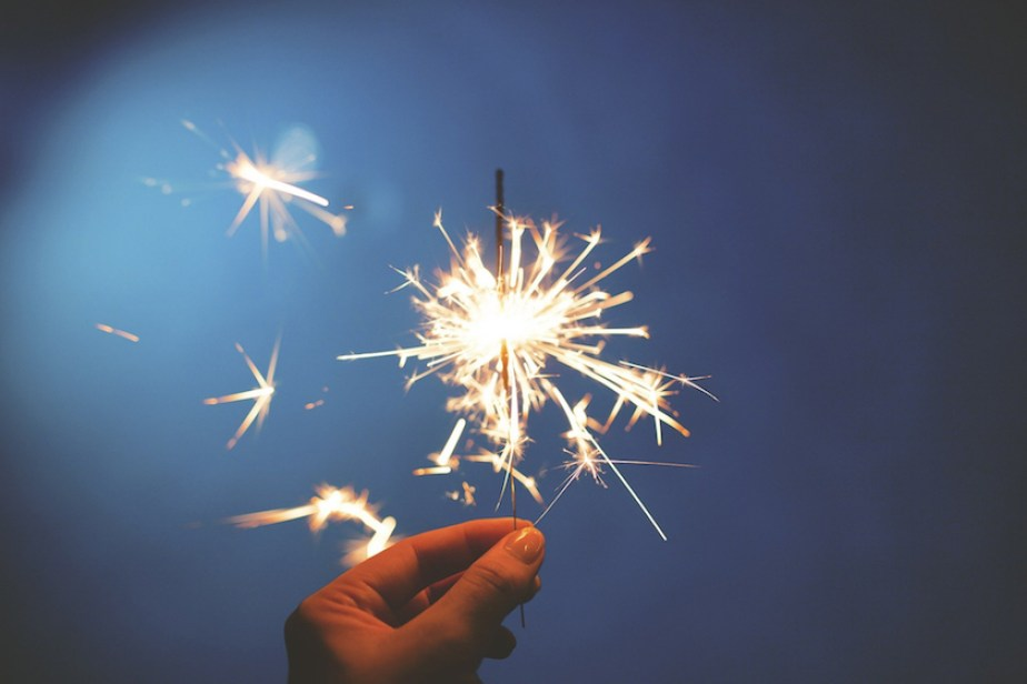 A photo of fingers holding a sparkler in a dark background.