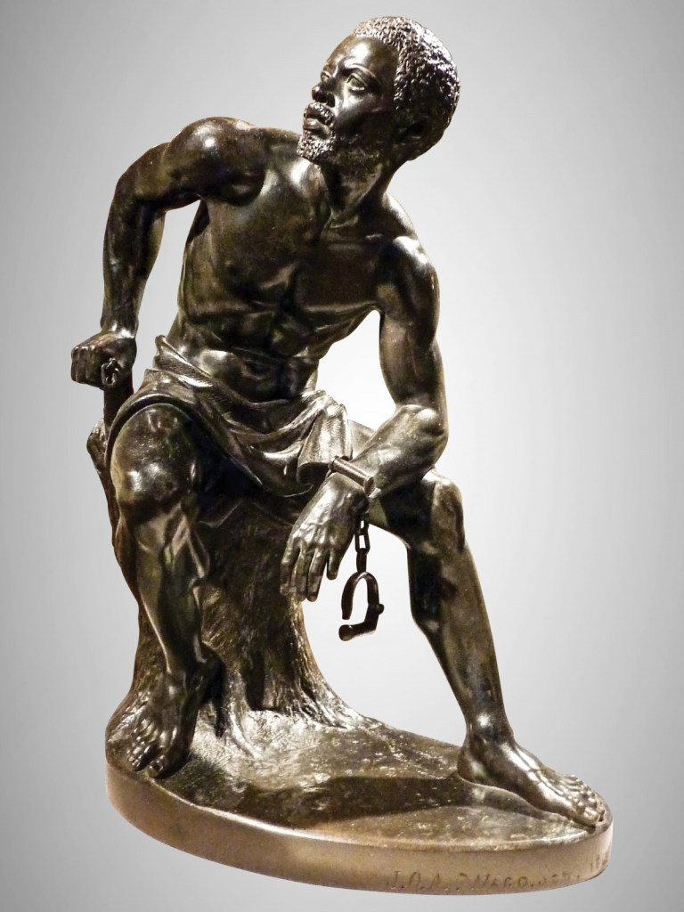 A bronze statue of a man with his chains being removed
