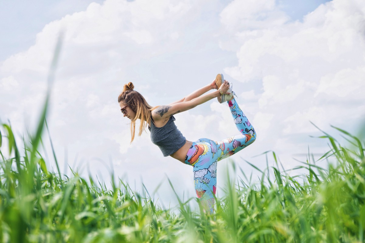 Woman stretching her leg in a grassy field