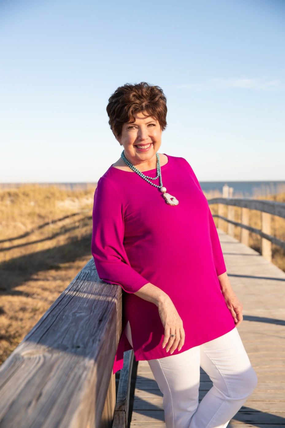 A woman in a pink blouse and white pants and large necklace standing on a boardwalk on a beach in the sunshine, smiling at the camera.