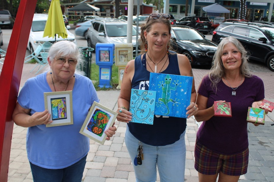 Three women standing outside holding up multiple pieces of different colored art pieces, with parked cars in the back.