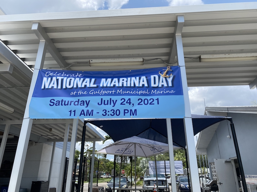 """A photo of a banner spread out over the entrance to a building that reads """"National Marina Day"""" in blue and white."""