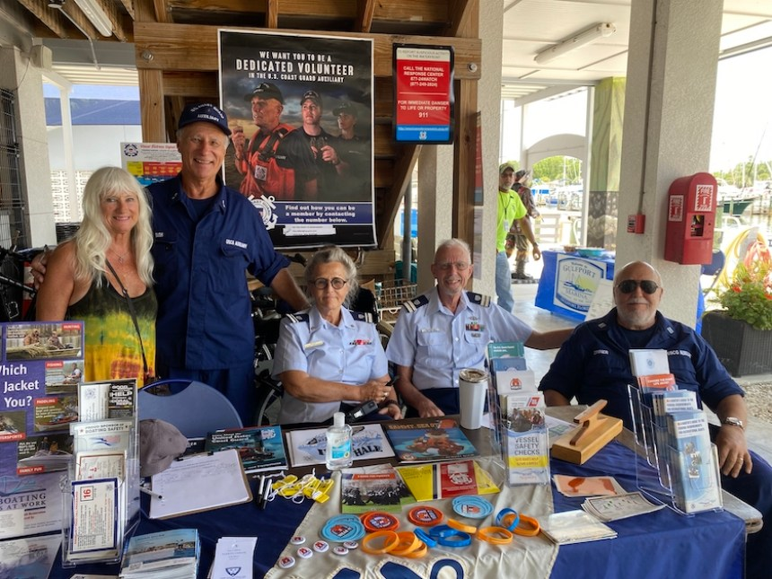 A photo of a group of people, some in Coast Guard uniform, sitting behind a table filled with informational pamphlets, all looking at the camera.
