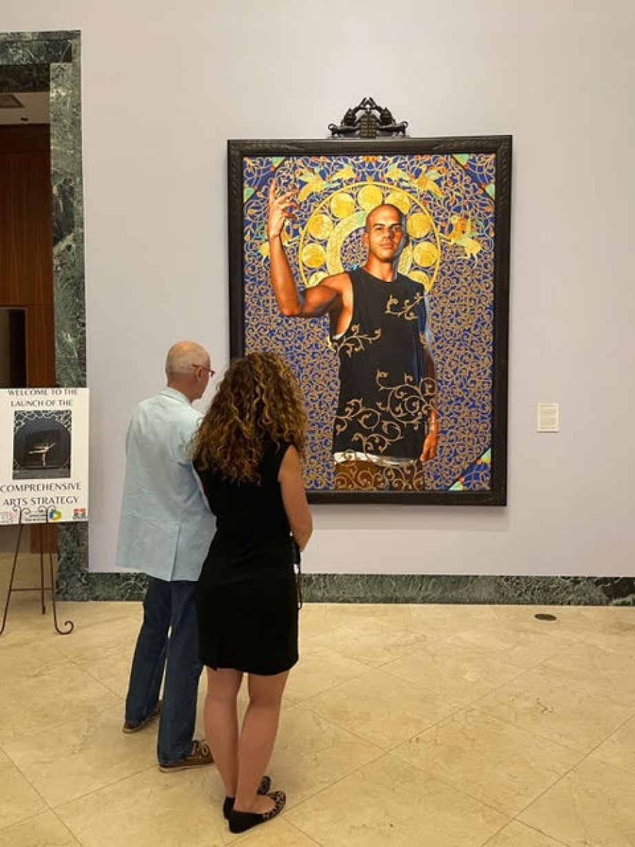 A man and a woman in a museum looking at a large piece of art featuring a man in a sleeveless black t-shirt with hand raised surrounded by golden symbols.