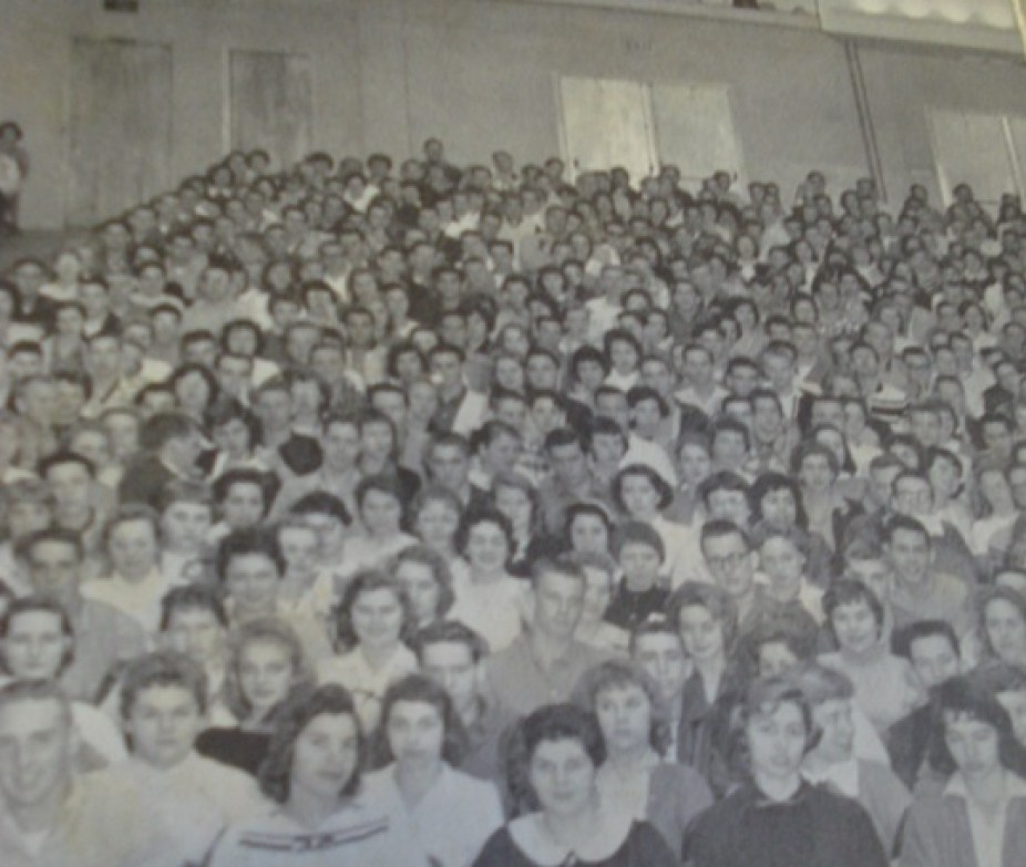 An old black and white photo of an auditorium full of high school students.