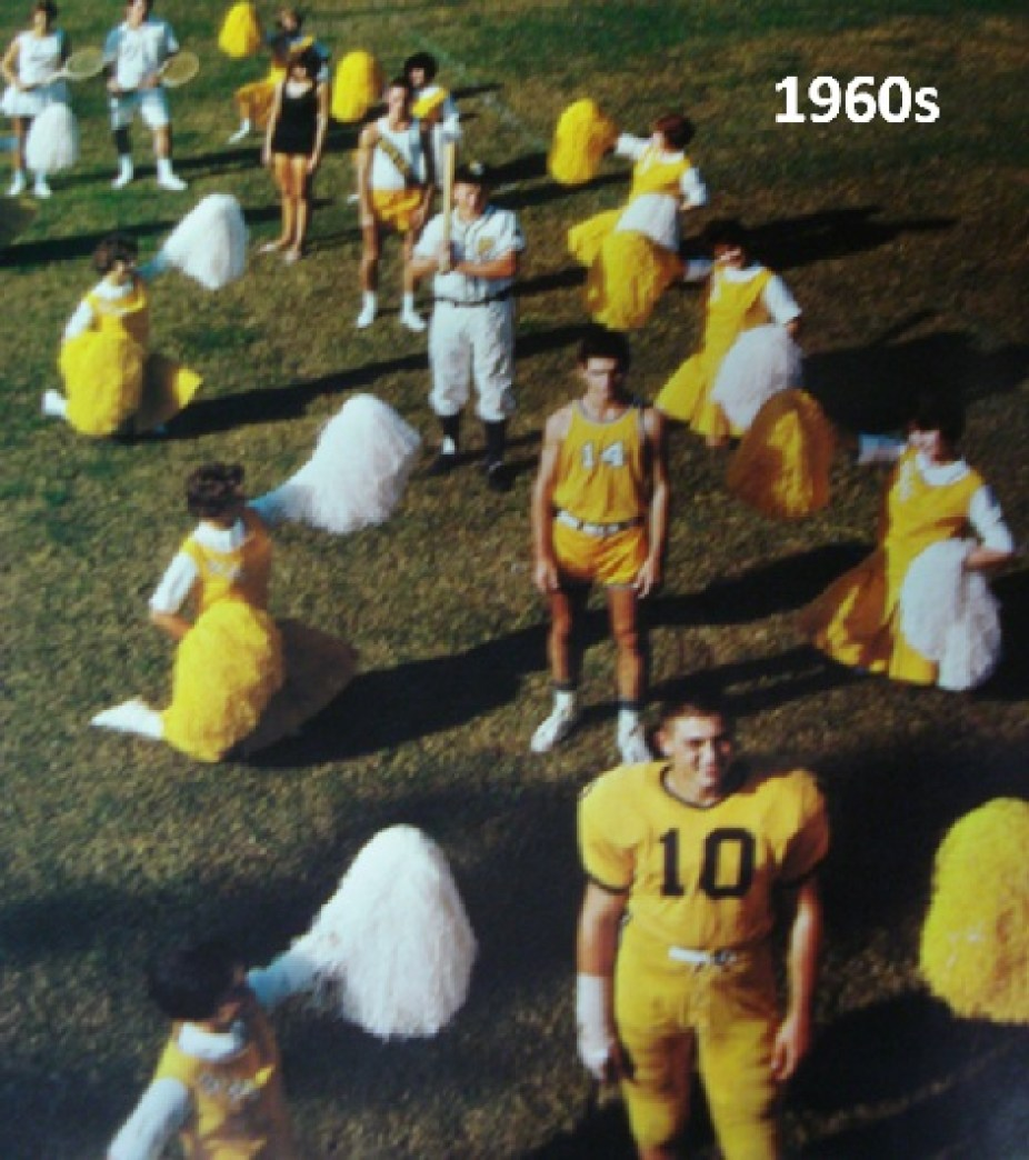 An old photo of boys in yellow football uniforms with cheerleaders standing around them on a field.