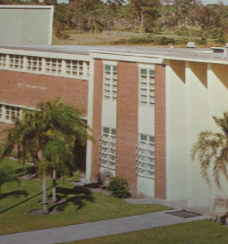 An old color photo of a high school building in red brick and concrete with palm trees.