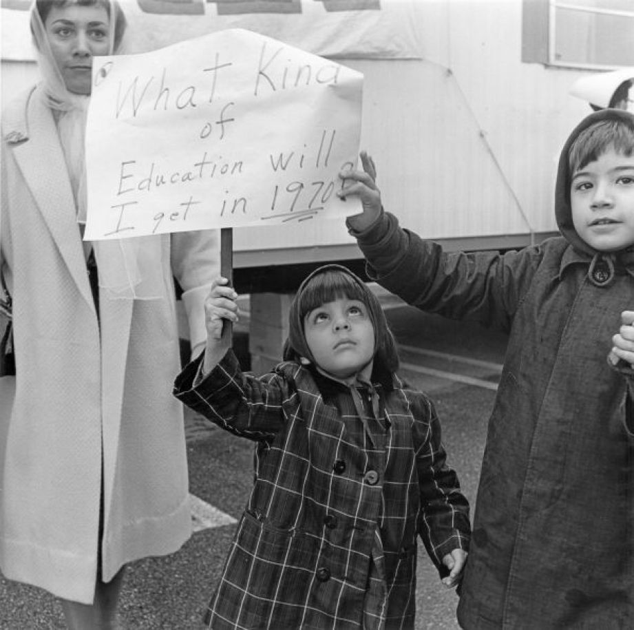 """An old black and white photo of a woman with two children in coats holding up a sign that reads """"What kind of education will I get in 1971"""""""