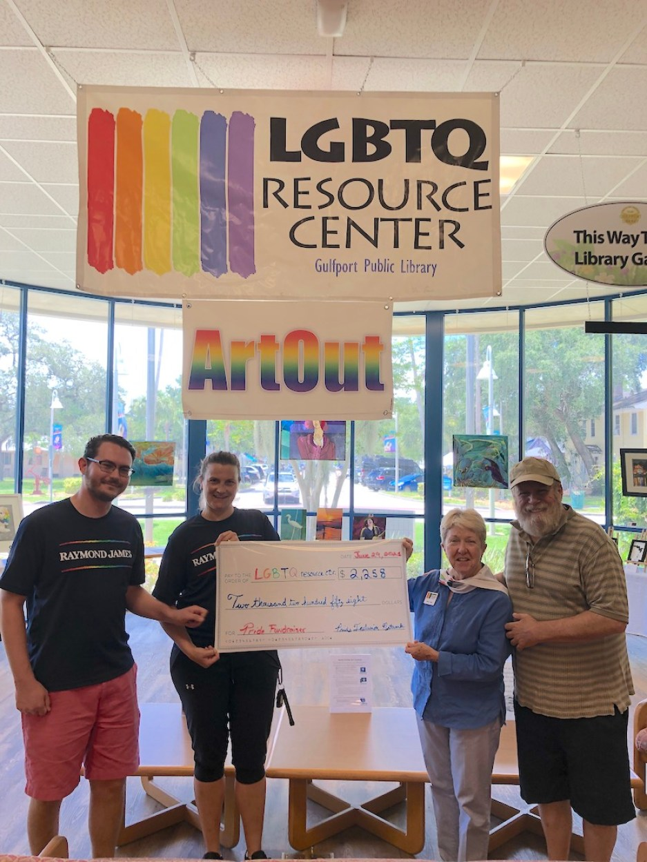 """Four people stand with a ceremonial check in a library underneath signs that read """"LGBTQ Resource Center"""" and """"ArtOut"""""""
