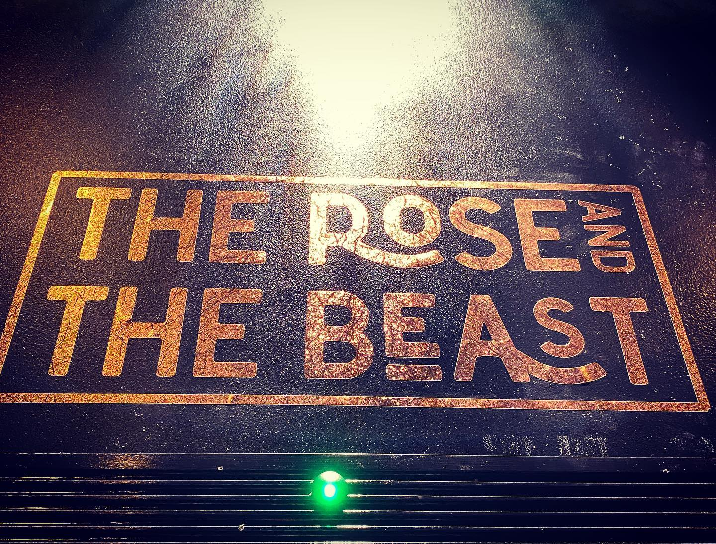 """A photo os a theater poster with a light shining on it at the top that reads """"The Rose and The Beast"""" in red letters in a red box on black background."""
