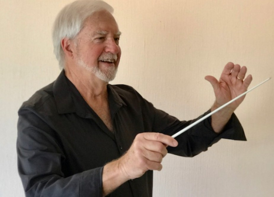 A man in a black shirt and white beard conducting.