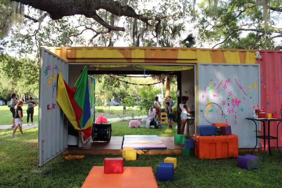 A shipping container repurposed into a art learning space in a park.