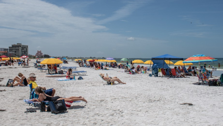A photo of people on the beach with colorful umbrellas.