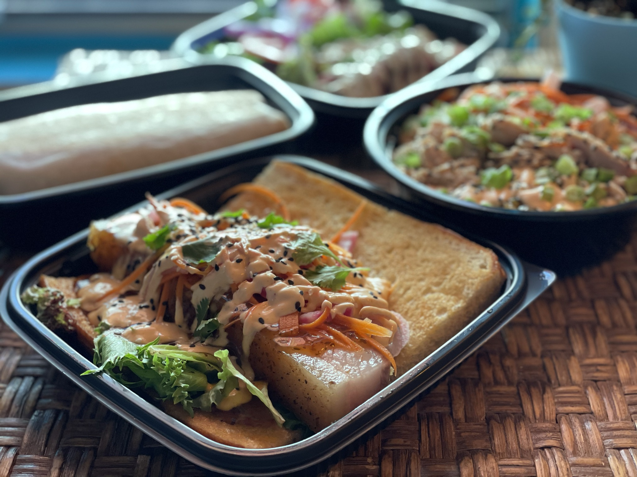 A photo of a black plastic tray of Mexican food with other dishes in the background.