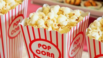 Red popcorn bucket with buttery popcorn over flowing
