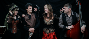 The band Gypsy Star -four people smiling against a black background.