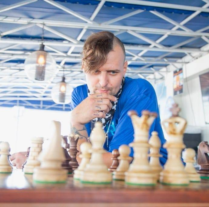 Kyle Kramer in a blue shirt ponders a chess board