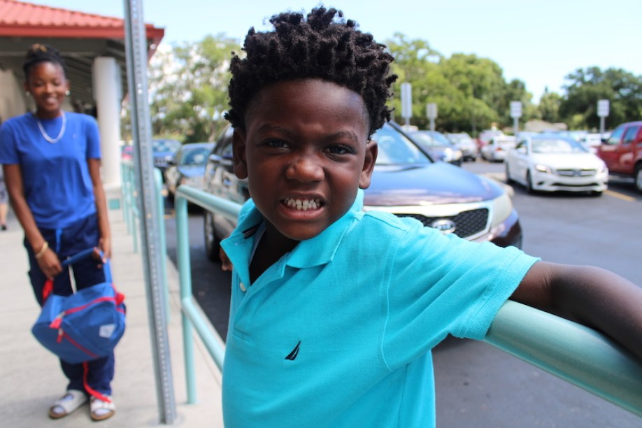 A young boy in a blue shirt outside next to a school railing smiling at the camera.