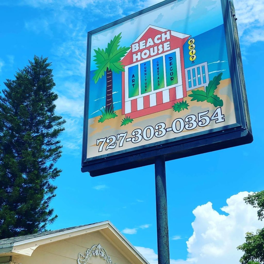 """A photo of a sign with a pink house on it that reads """"Beach House 727-303-0354"""""""