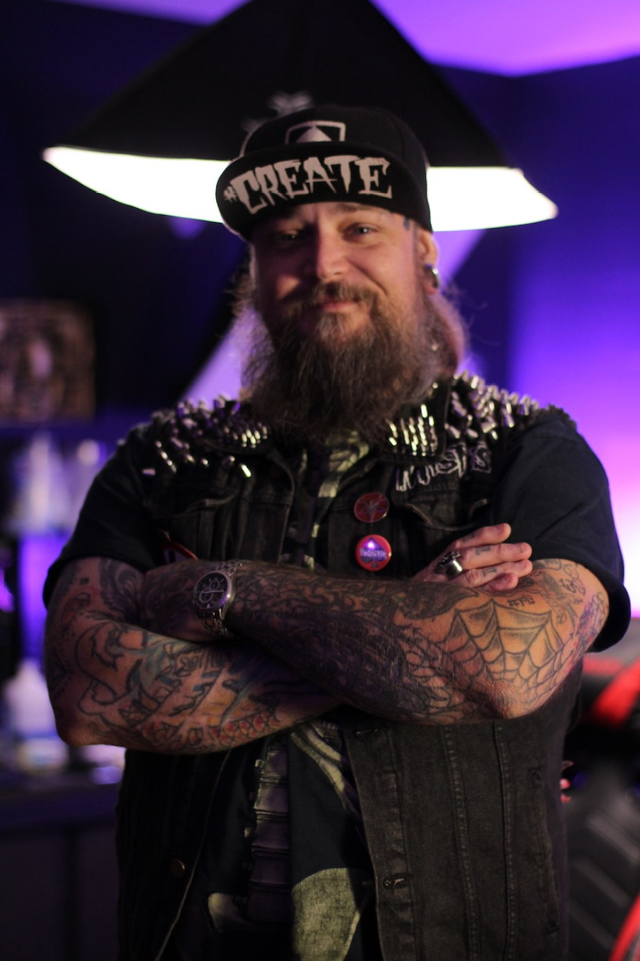 A tattooed man with a beard and hat looking at the camera with his arms crossed.
