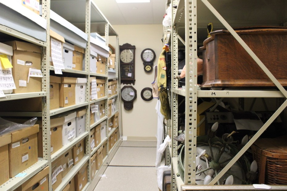A hallway of shelves with boxes of files and four clocks at the end of the hall.