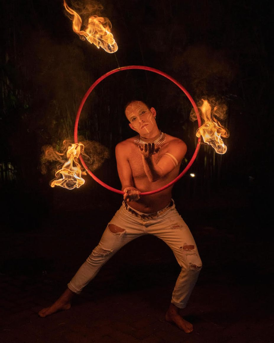 A photo of a man with no shirt and white pants performing with a ring with three flames coming off of it. .
