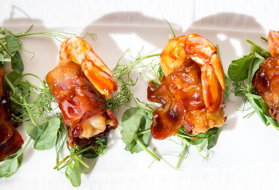 A photo of a white plate with bacon-wrapped shrimp and green garnish.