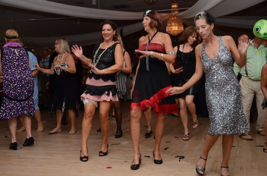 A photo of women dressed in flapper dresses dancing at a costume party.