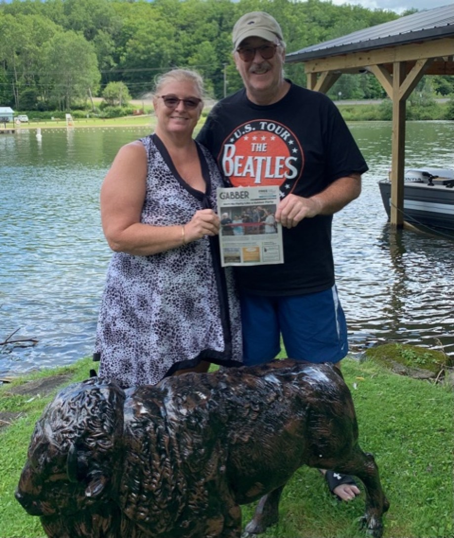 A photo of a man and a woman standing on a lakeshore in the grass smiling at the camera, holding a Gabber newspaper in front of a statue of a buffalo.
