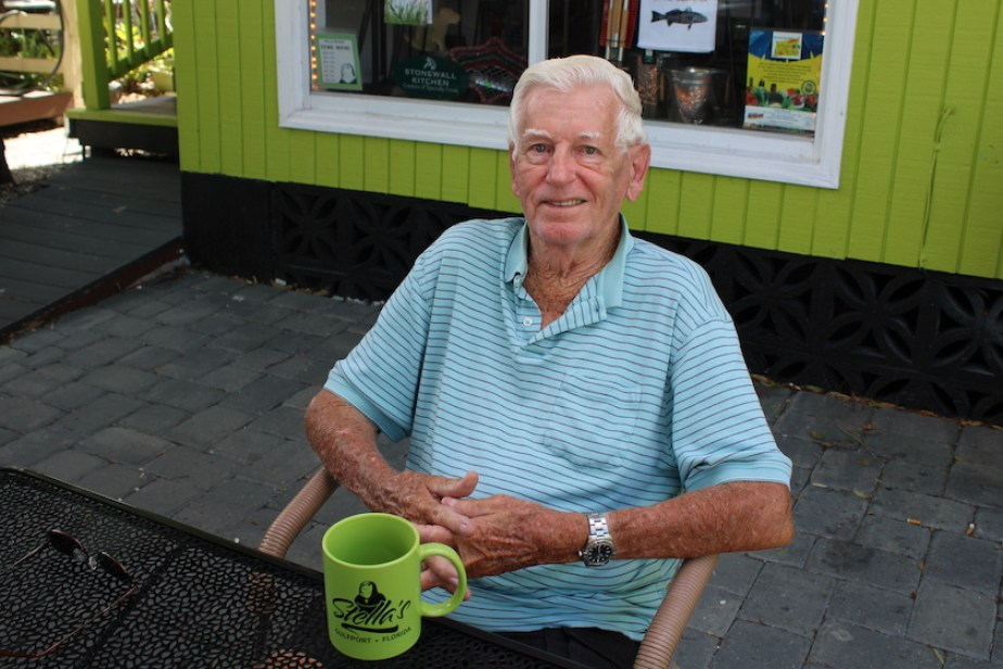 An older man with a green coffee mug sitting at a table in a courtyard.