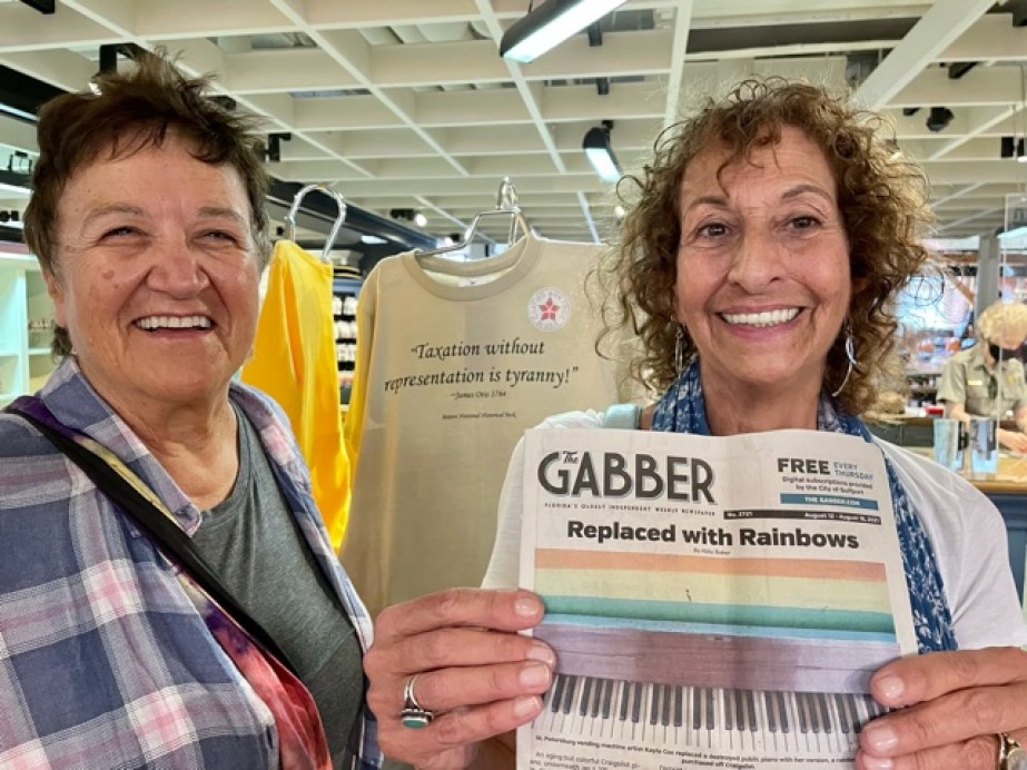 A photo of two women with one holding a copy of the Gabber Newspaper.