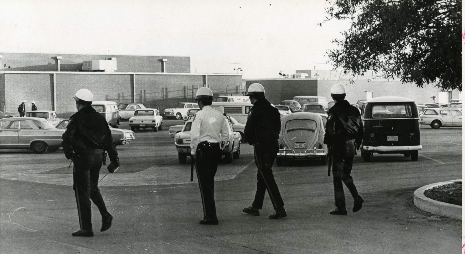 An old black and white photo of police officers with helmets walking on to a school parking lot.