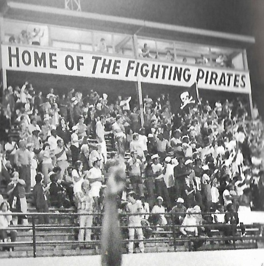 """A black and white photo of a large crowd under a sign that reads """"Home of the Fighting Pirates"""""""