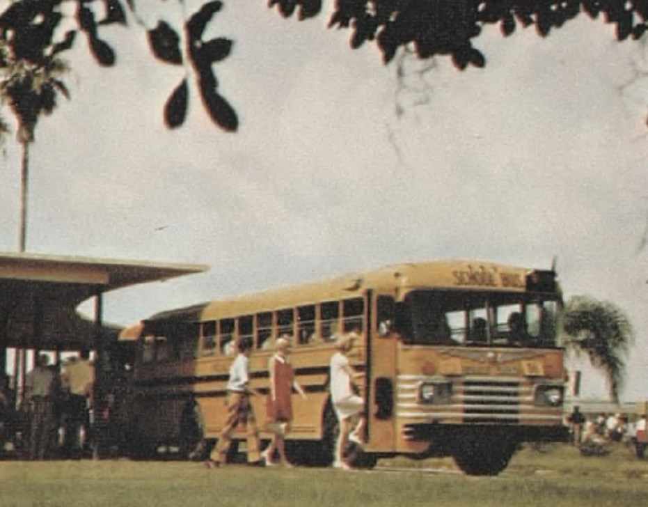 An old color photo of a yellow school buss with students standing near it.