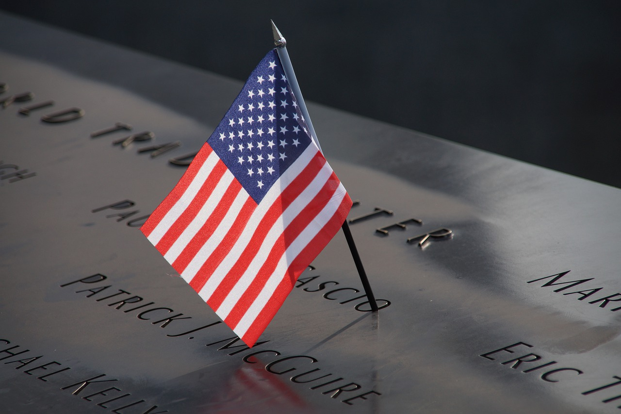 A photo of a small US flag on a black memorial stone.