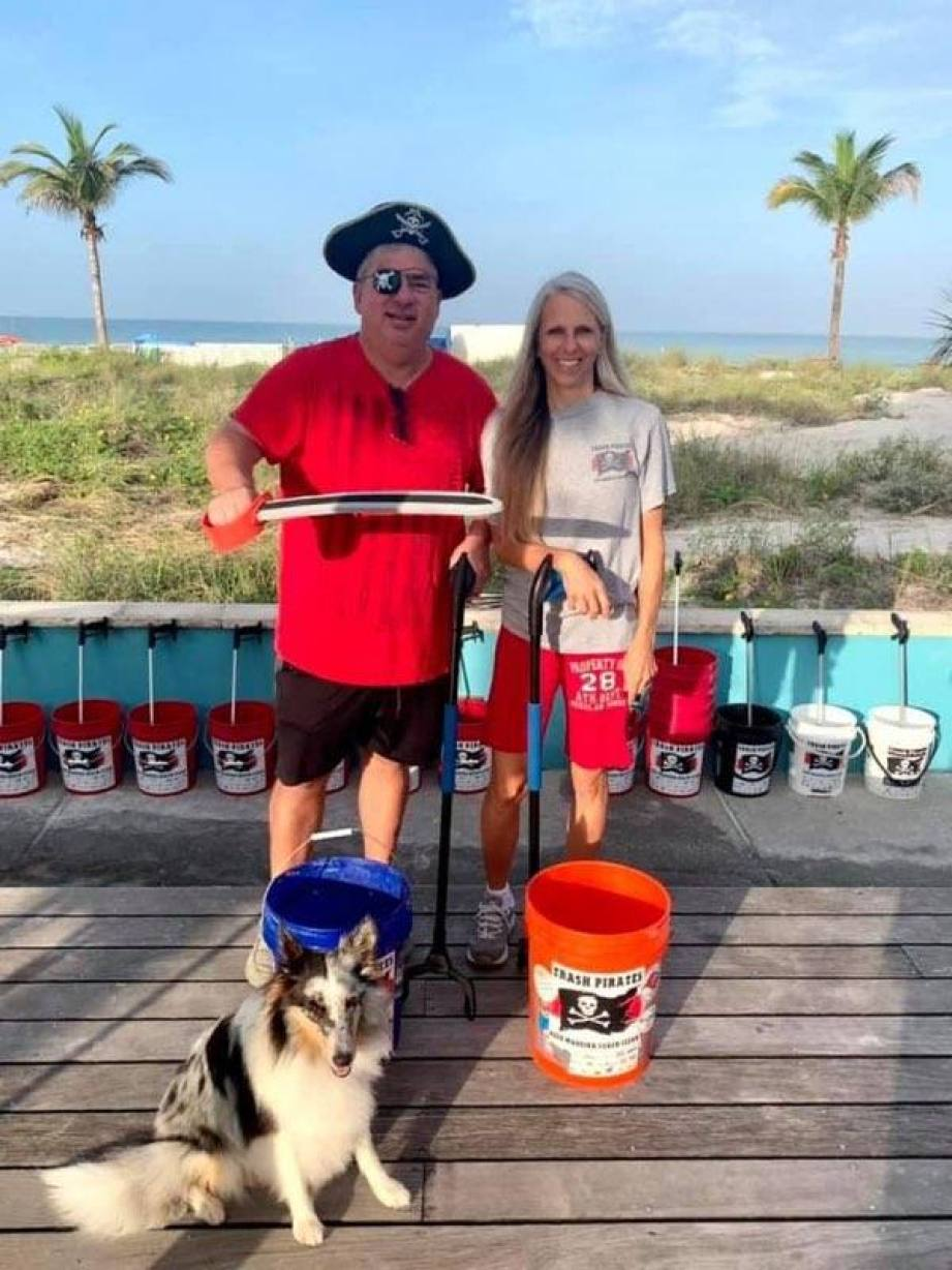 A man dressed as a pirate and woman stand on a deck near the beach with a dog and an orange bucket.