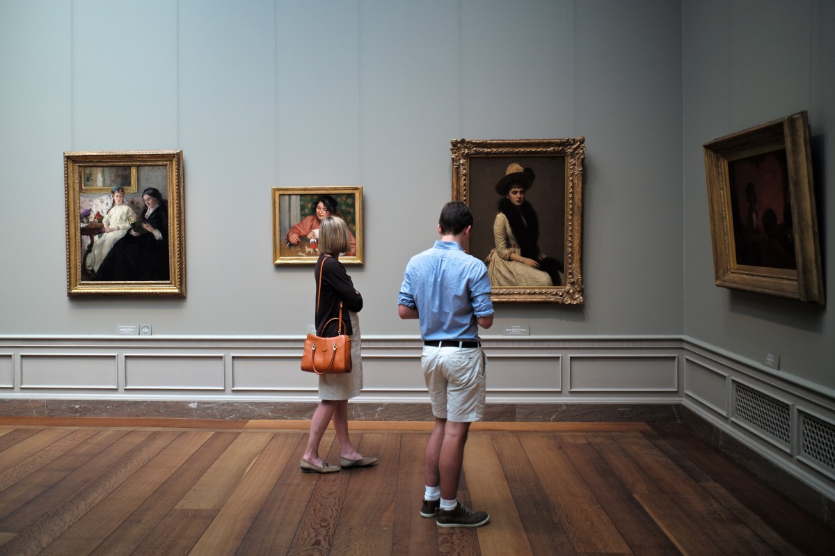 Two people walking in front of a painting in a museum